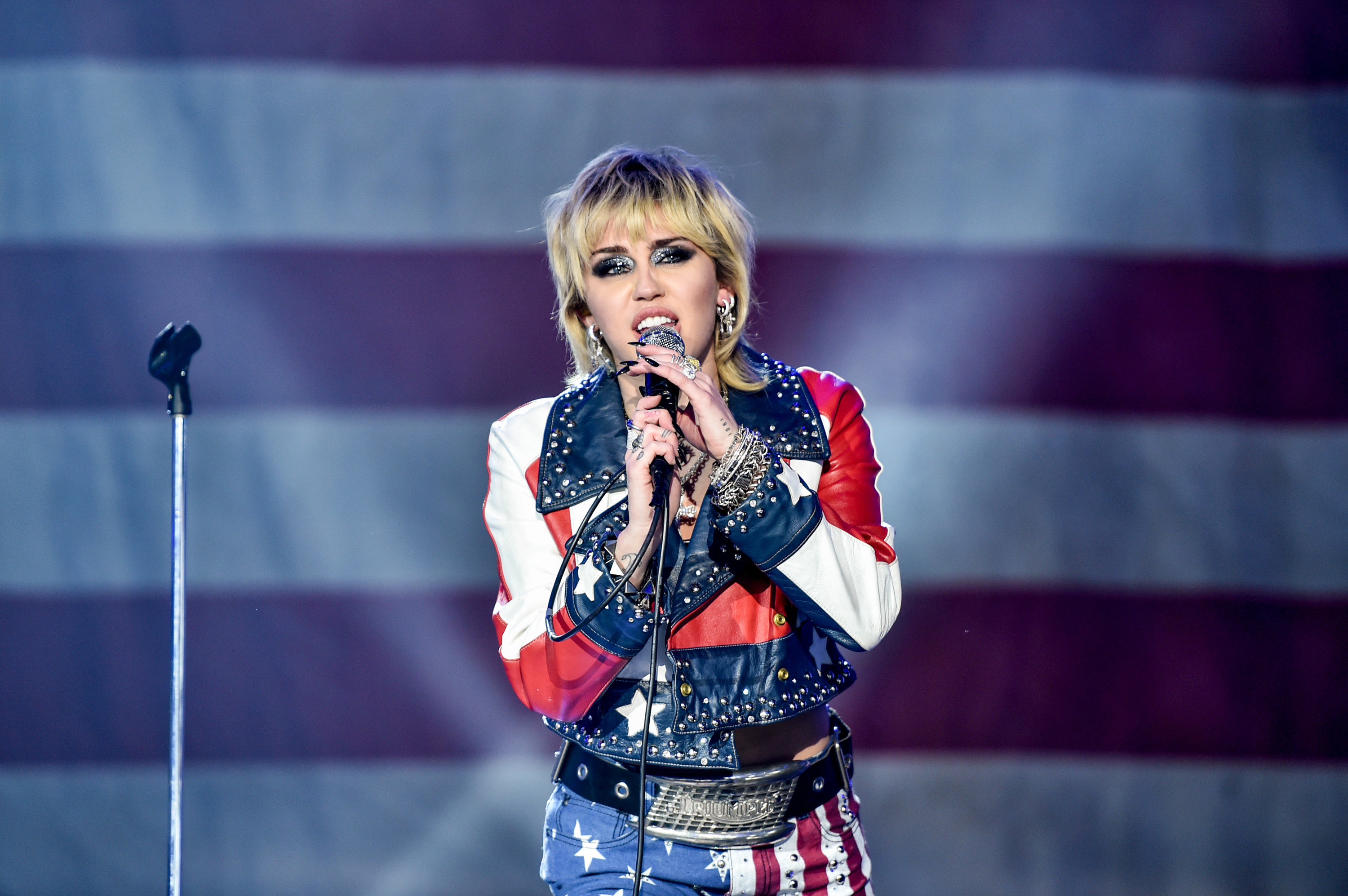 Miley Cyrus holds a microphone with both hands as she performs in front of an American flag