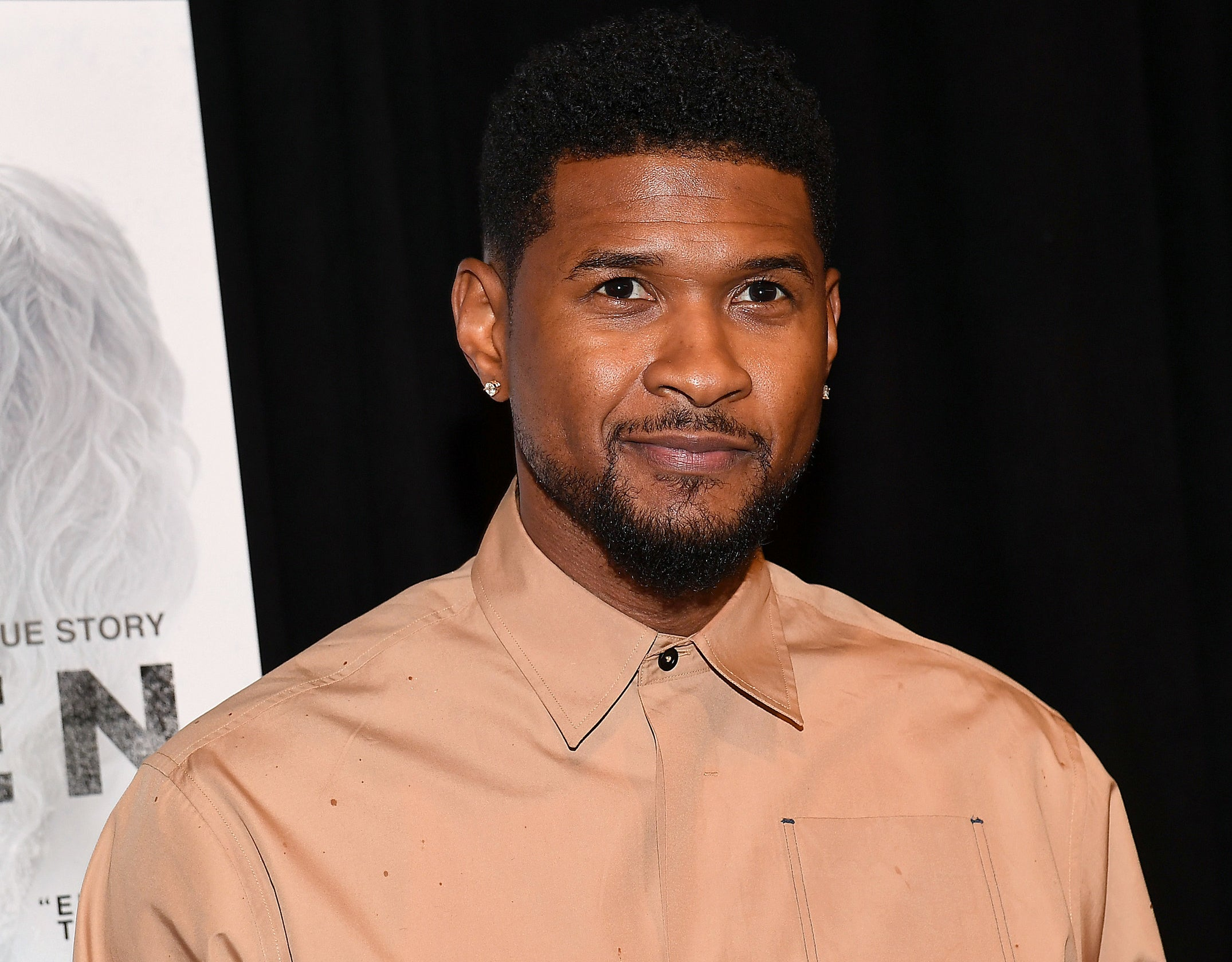 Usher looks serious while wearing a beige button down