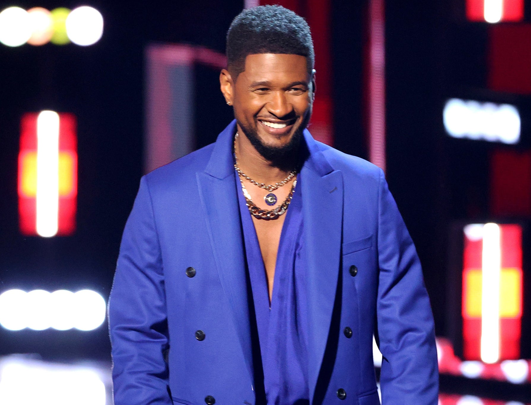 Usher smiles while wearing a blue suit on stage