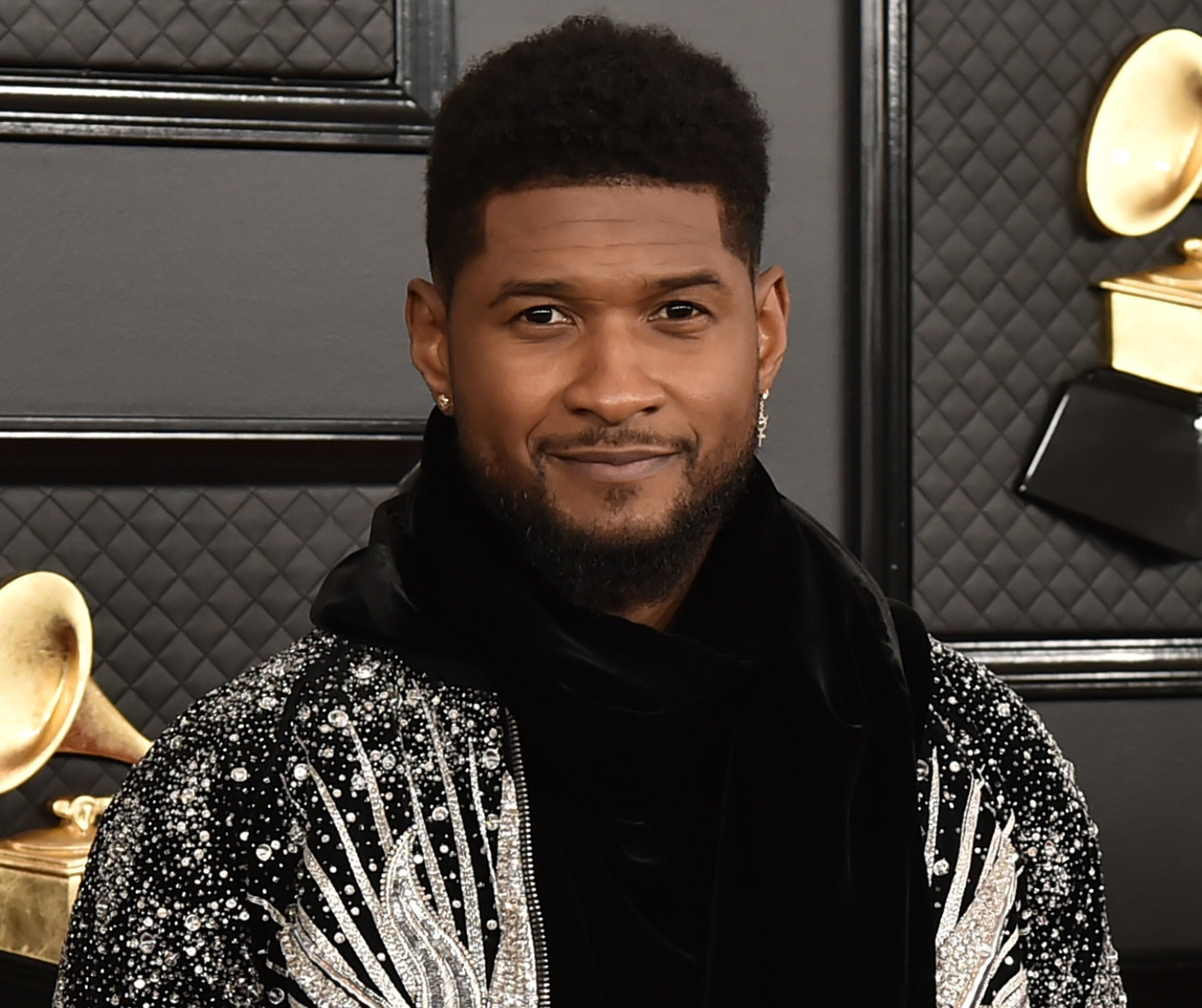 Usher wears a black hoodie and jacket with crystal embellishments on a red carpet