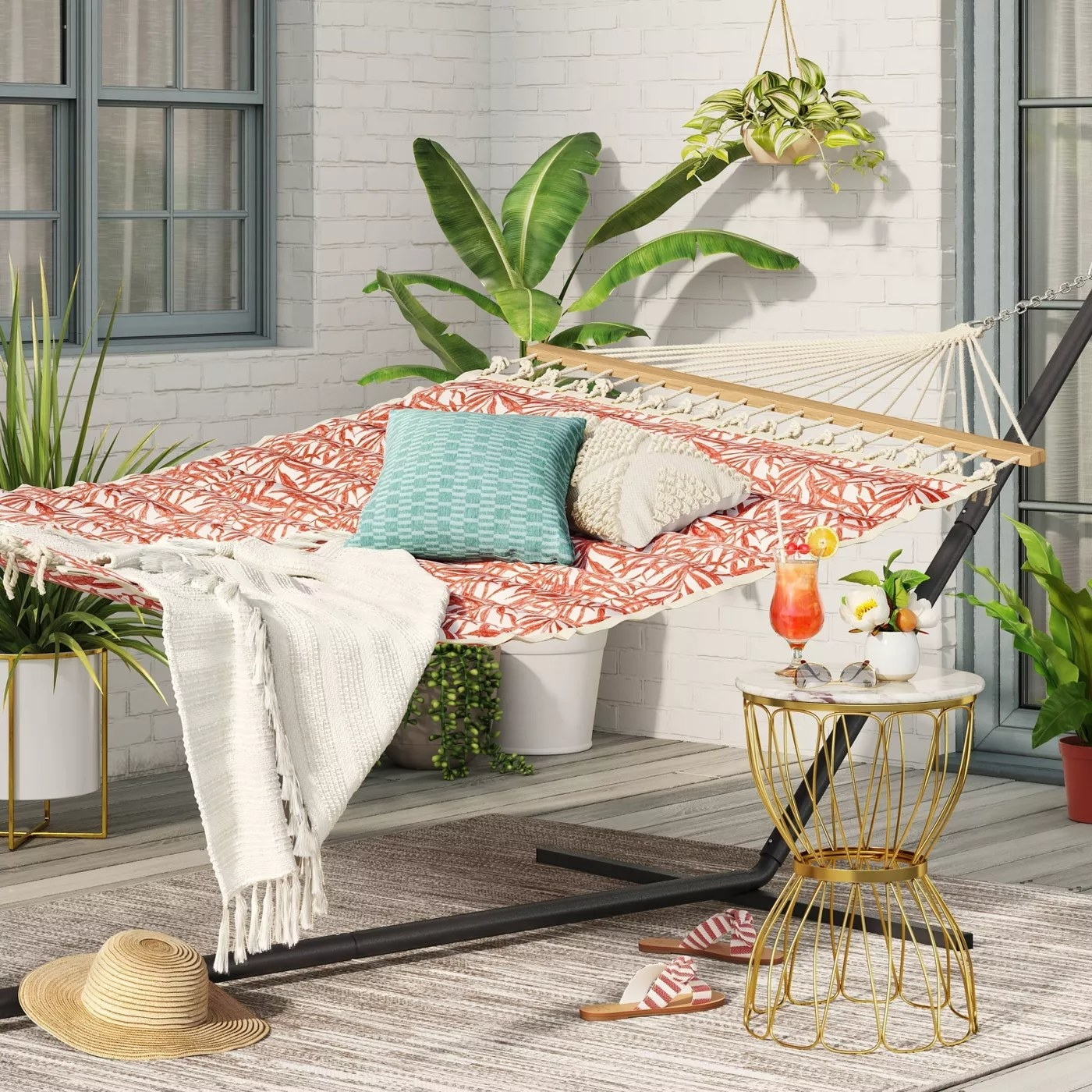 The padded hammock with a peach print on a deck