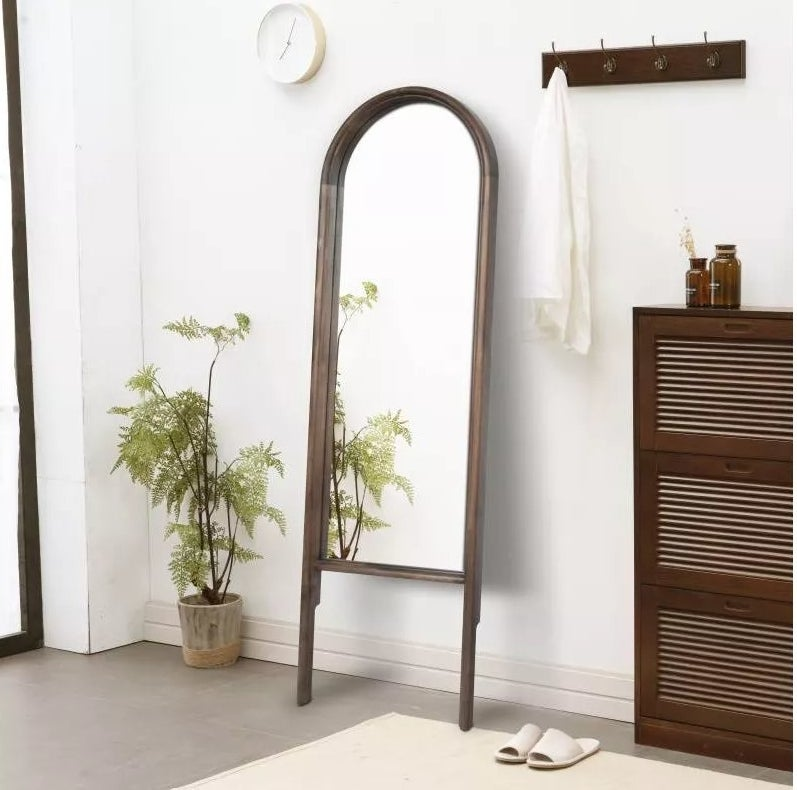 The arched floor mirror leaning against a wall