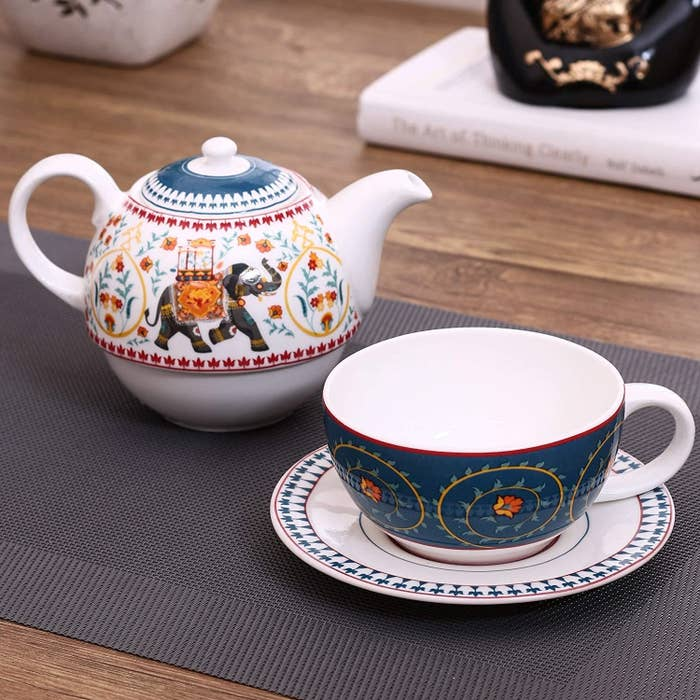 A teacup and teapot set with an elephant and flowers on it