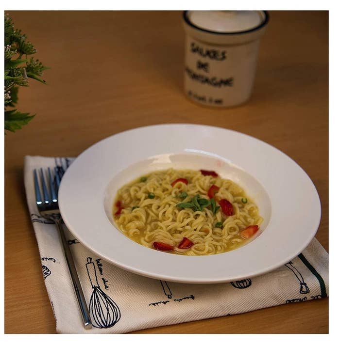 A plate with noodles in it next to forks and a napkin