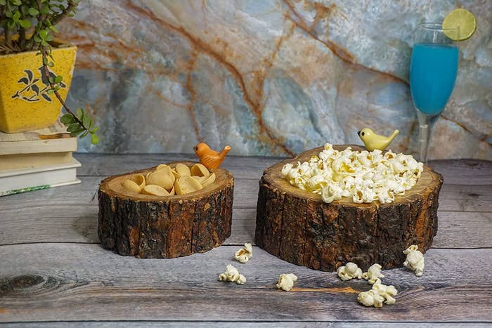 Two tree-trunk shaped bowls with popcorn and food items in it