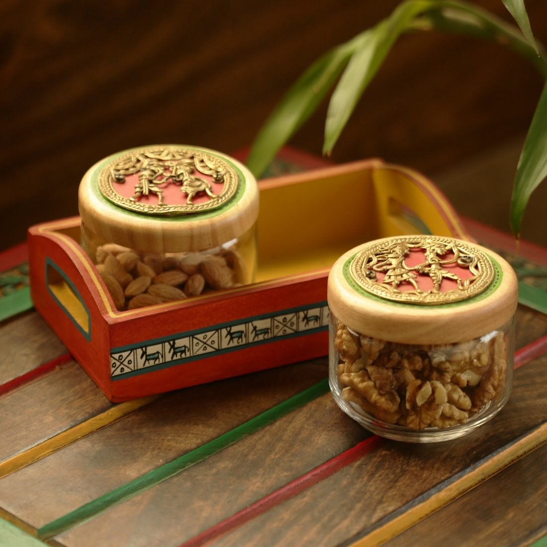 A pair of Dhokra art jars with walnuts and almonds in them. One of them is kept in a wooden tray and the other is kept tray near the tray.