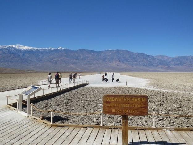 A flat and desolate desert landscape has people walking over a boardwalk.
