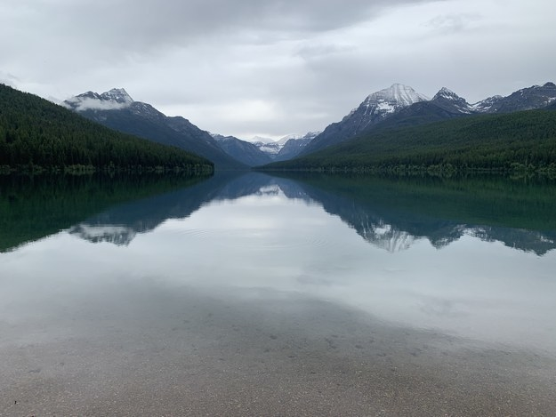 Glacier National Park's mountains are mirrored on the lake surface.