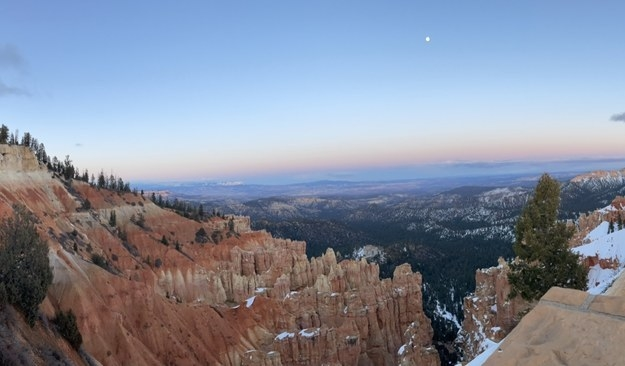 A tiny moon on top of the skyline looks down onto the trees-lined, sparse rock formations of Bryce Canyon.