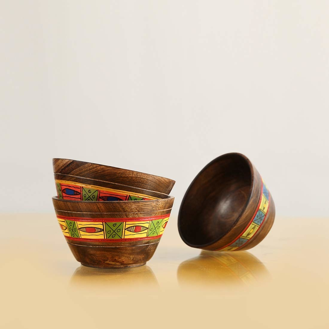 Three wooden bowls with a colourful band across their circumference
