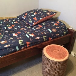 Reviewer using the tree trunk stool as a side table near their bed