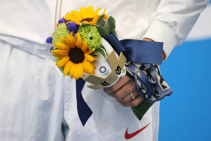 An Olympic athlete holding Tokyo's flower bouquet