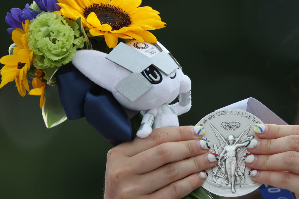 An Olympic athlete holding their silver medal and flowers