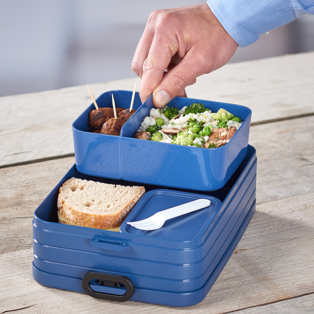 a person pulling out one of the compartments of the bento box lunch box