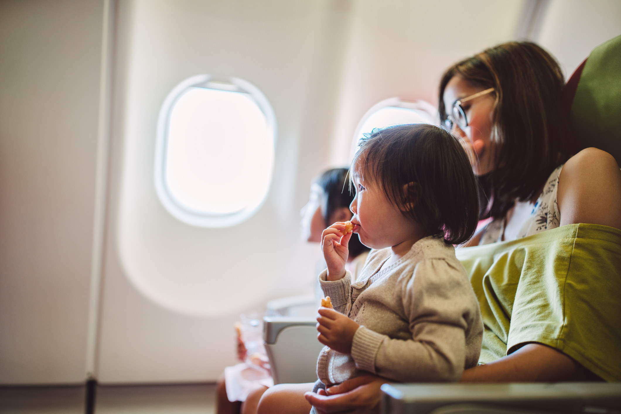 A mom feeding her baby on an airplane