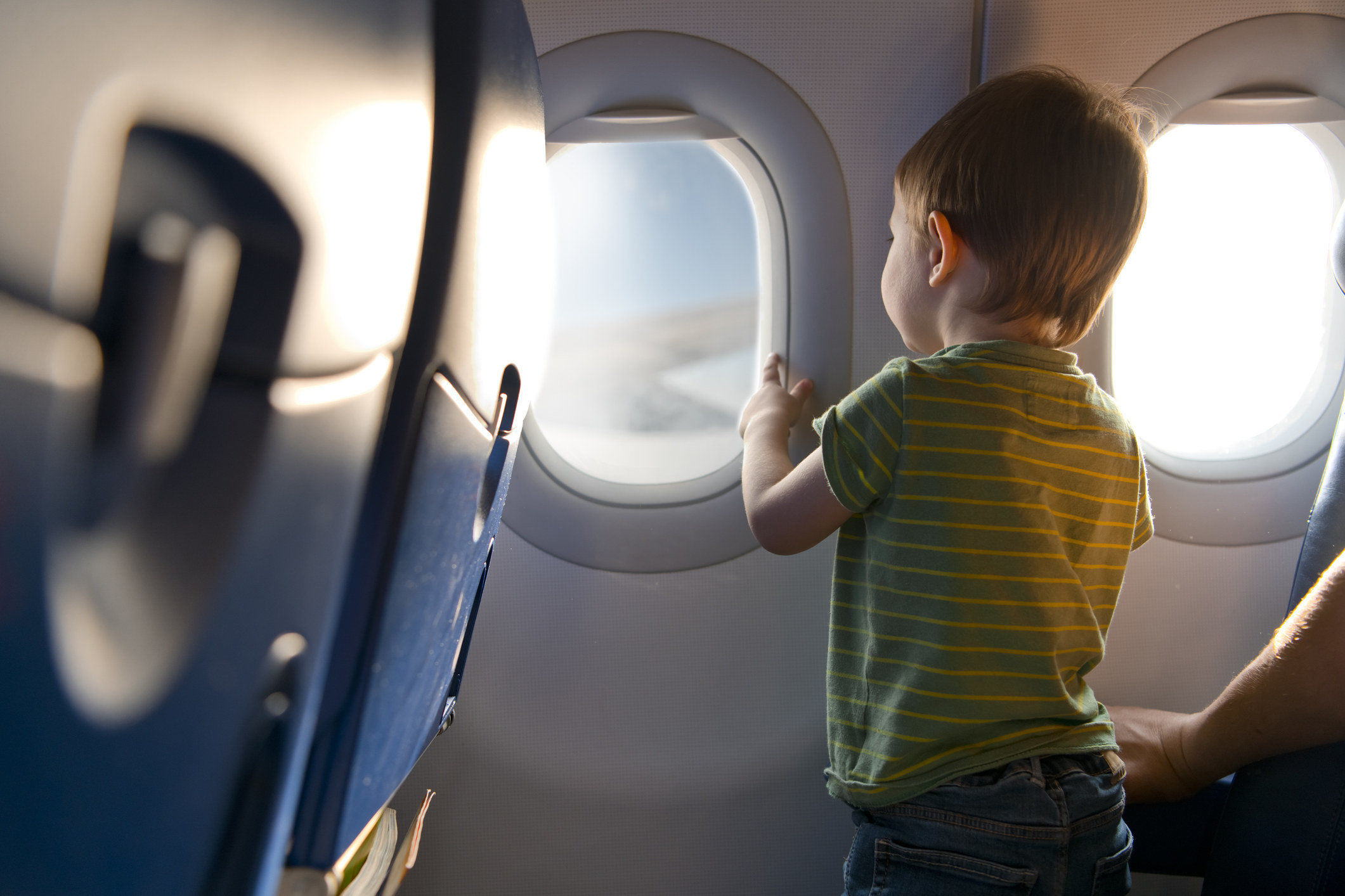 A child looking out an airplane window