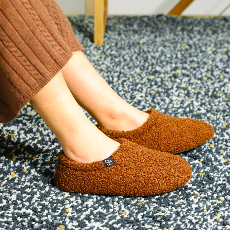 A person wearing the slippers on a carpet