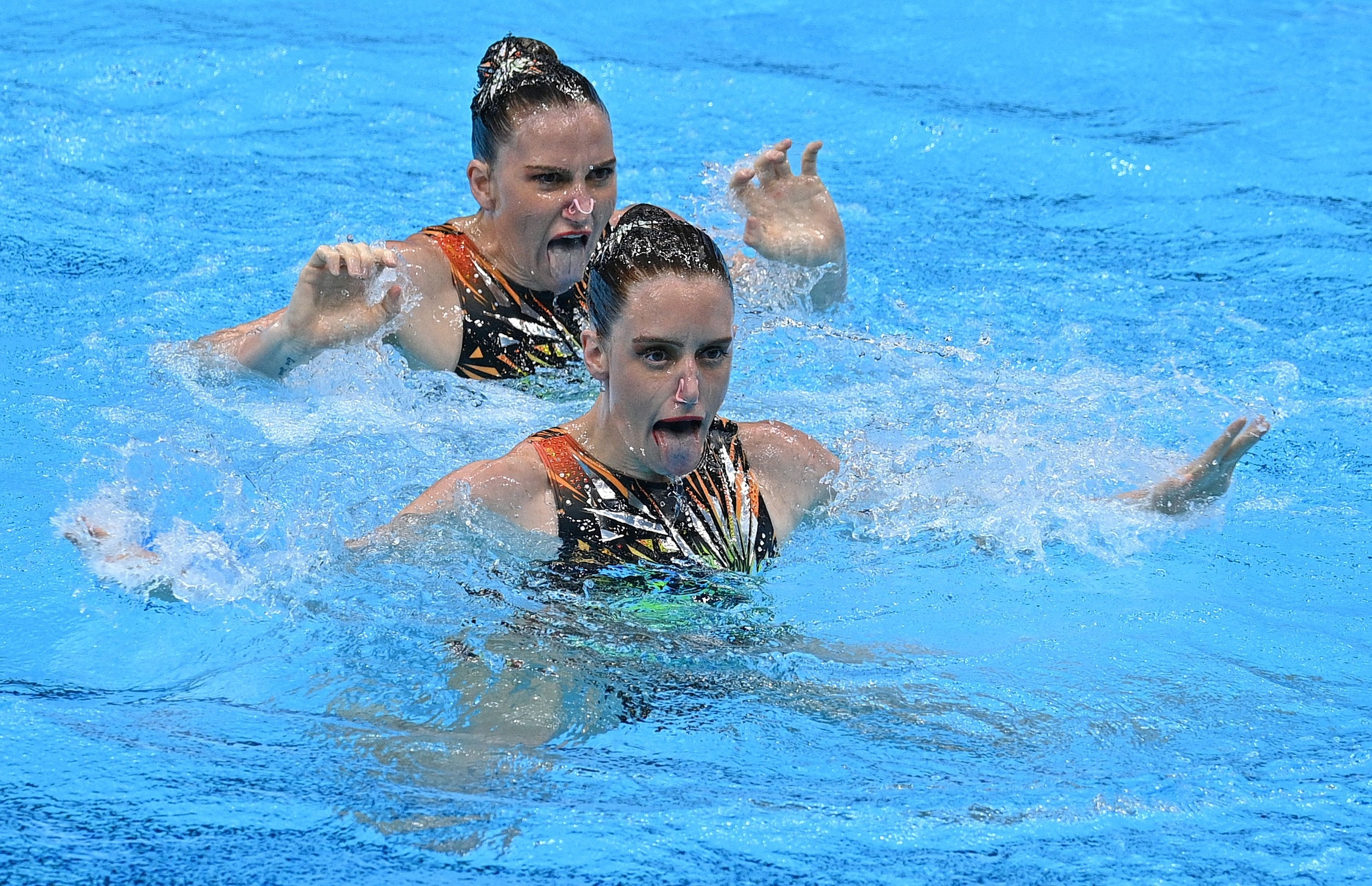Two women swimmers hold their heads above water in the pool and stick their tongues out at the Tokyo Olympics