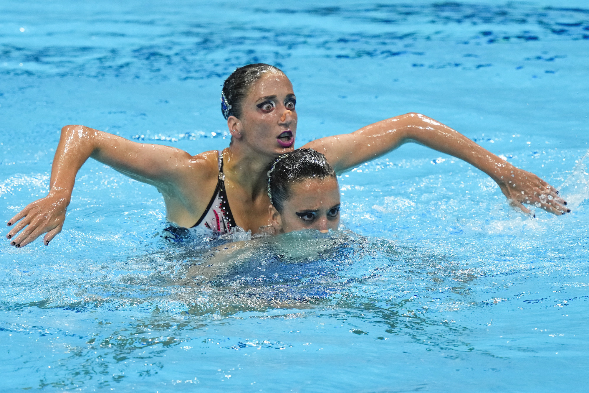 One swimmer stands behind another with their head above the other's in a pool
