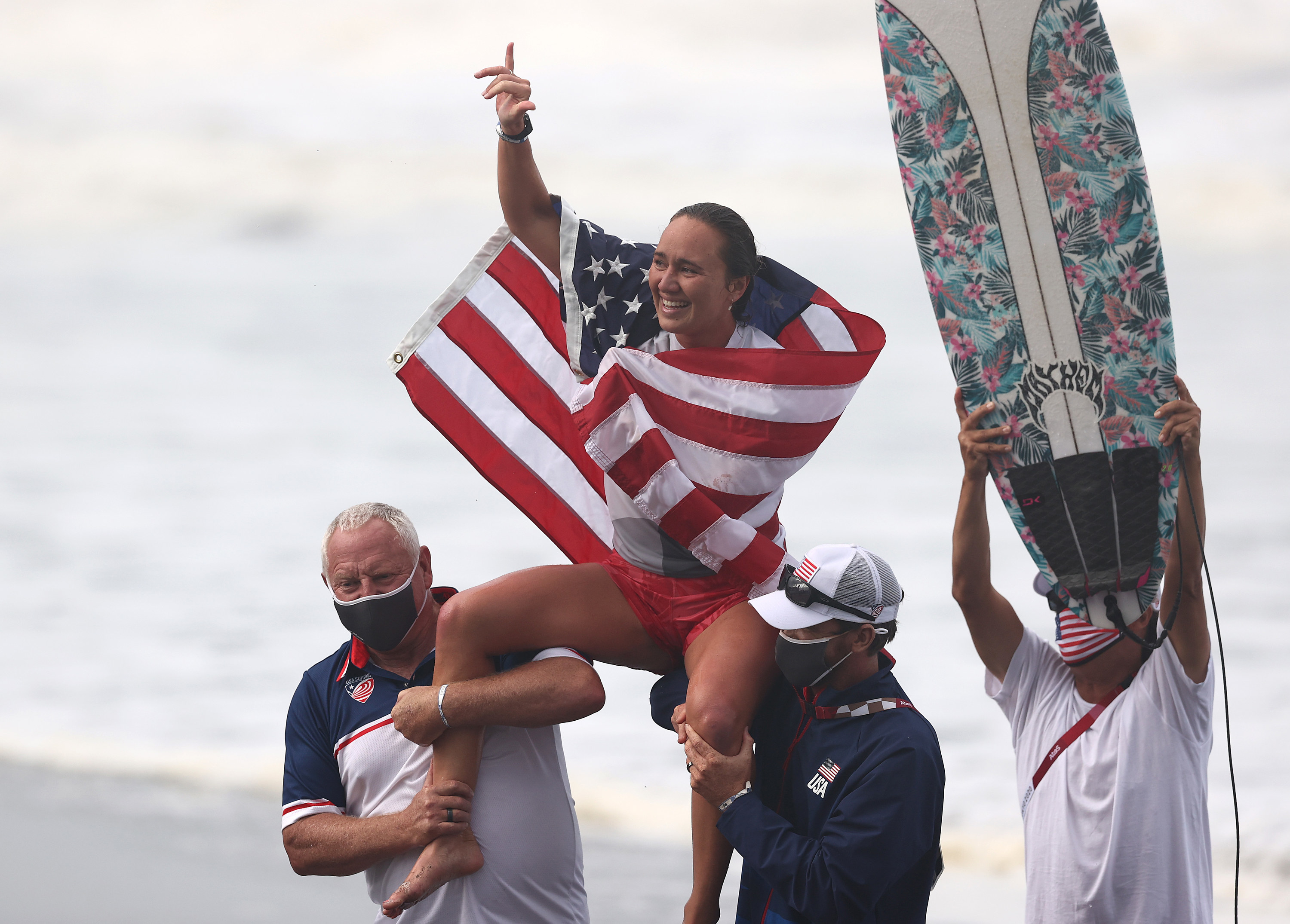 Moore sitting on the shoulders of coaches with a flag draper around her shoulders to celebrate winning the Gold Medal after her final match