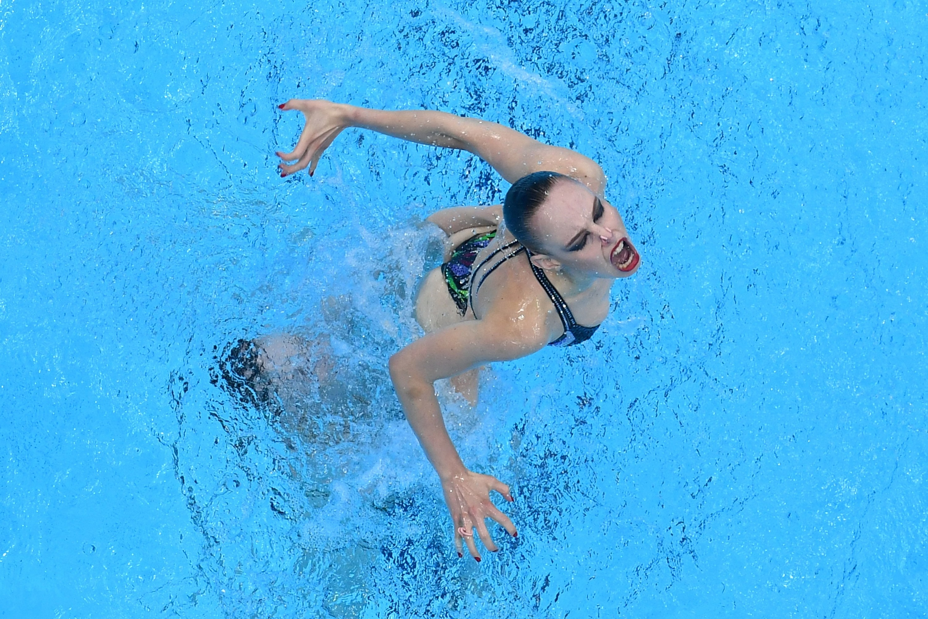 An overhead view of a woman swimmer holding her head above water at the Tokyo Olympics