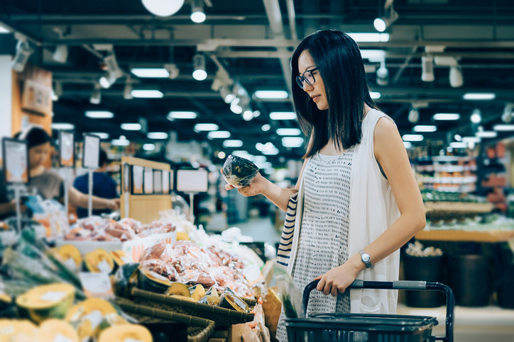 image of a woman in grocery store inspecting a piece of produce