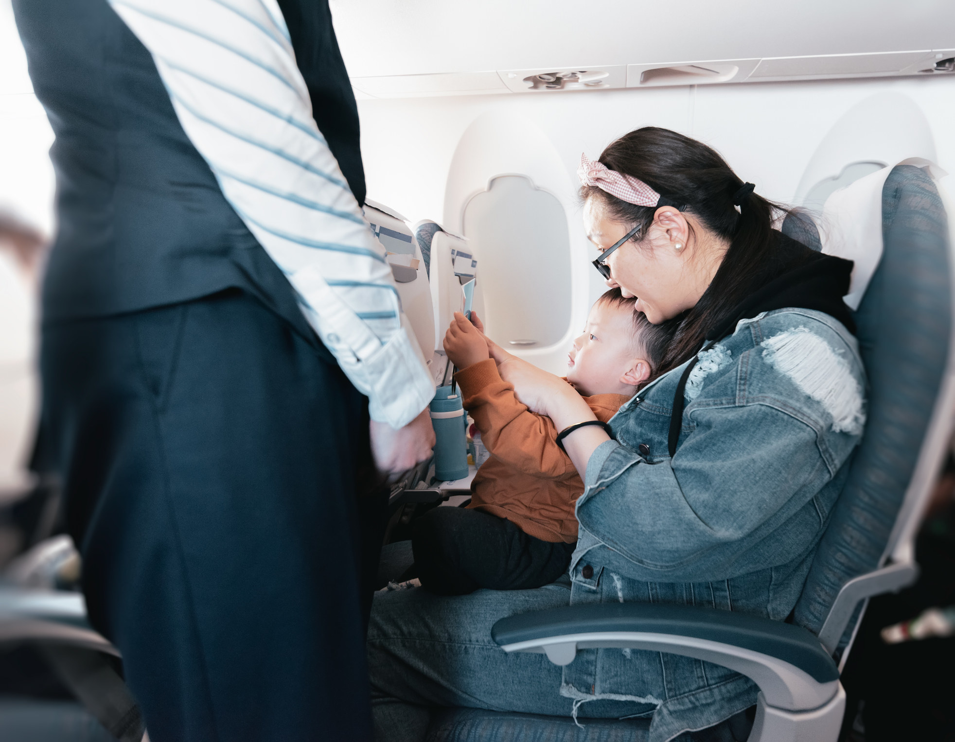 A mom and toddler sitting together on an airplane