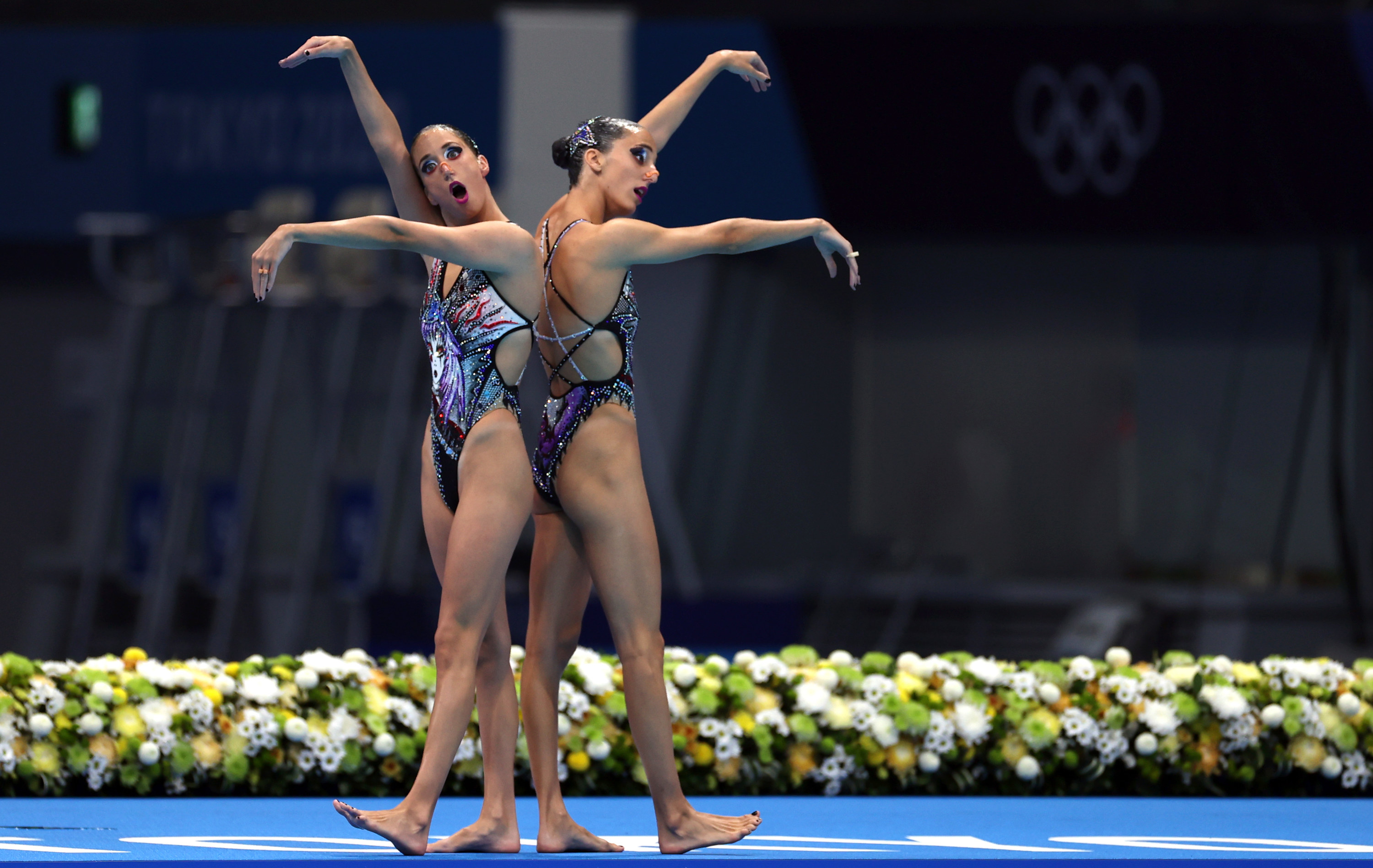 Two women swimmers stand back to back on a mat with their arms stretched before them in a performance