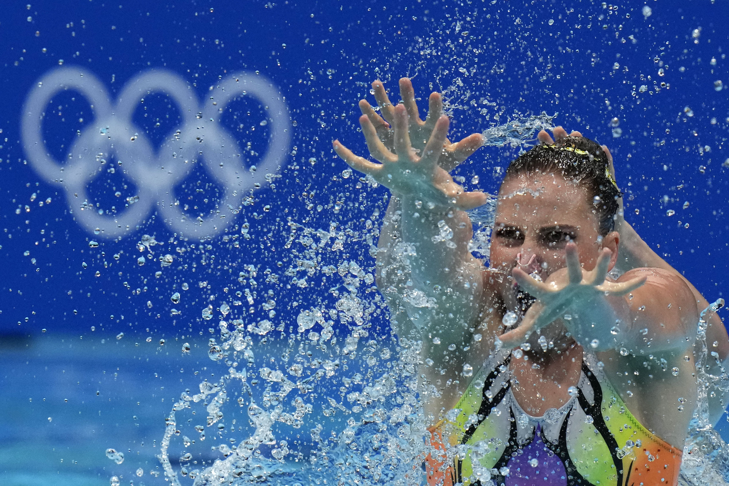 A woman swimmer holds her arms and spread fingers out before her, surrounded by droplets of water