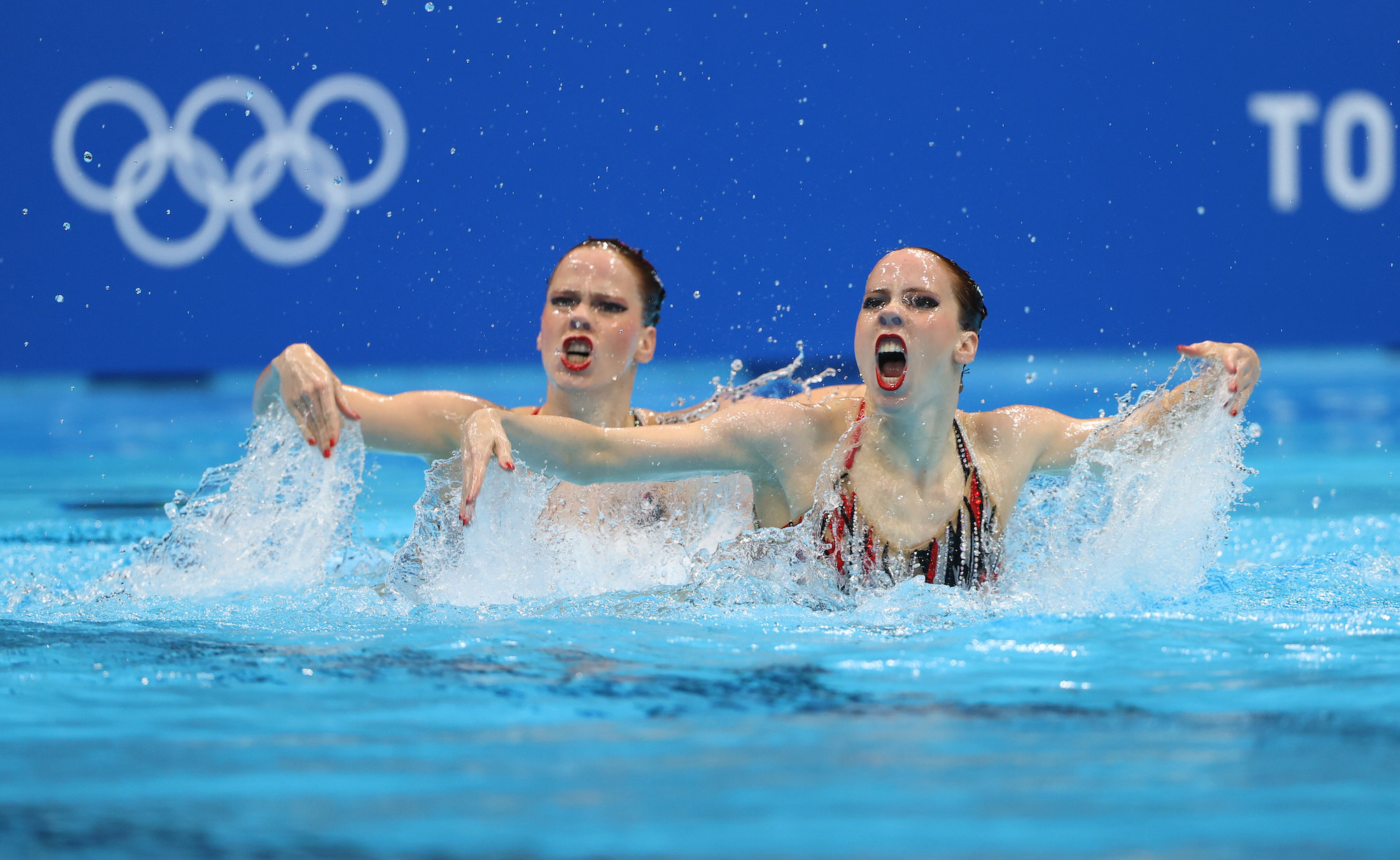Two women swimmers perform in the pool with their arms to the side