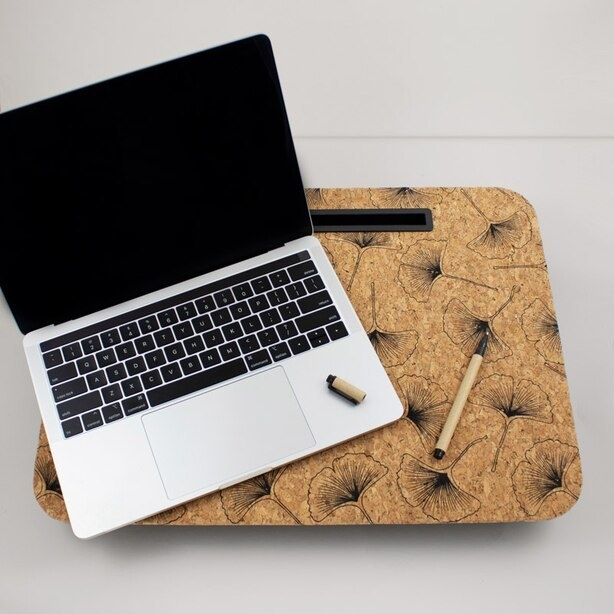 a laptop and pen on top of the cork laptop desk