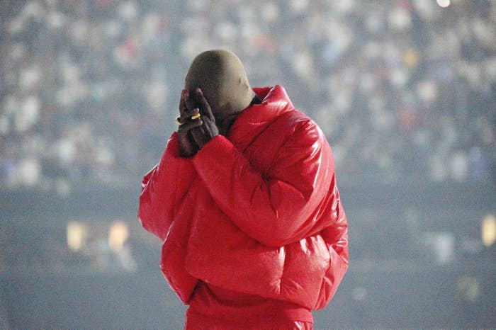 Kanye West is pictured wearing a red puffer coat and a mask over his head at the Donda album listening event in Atlanta
