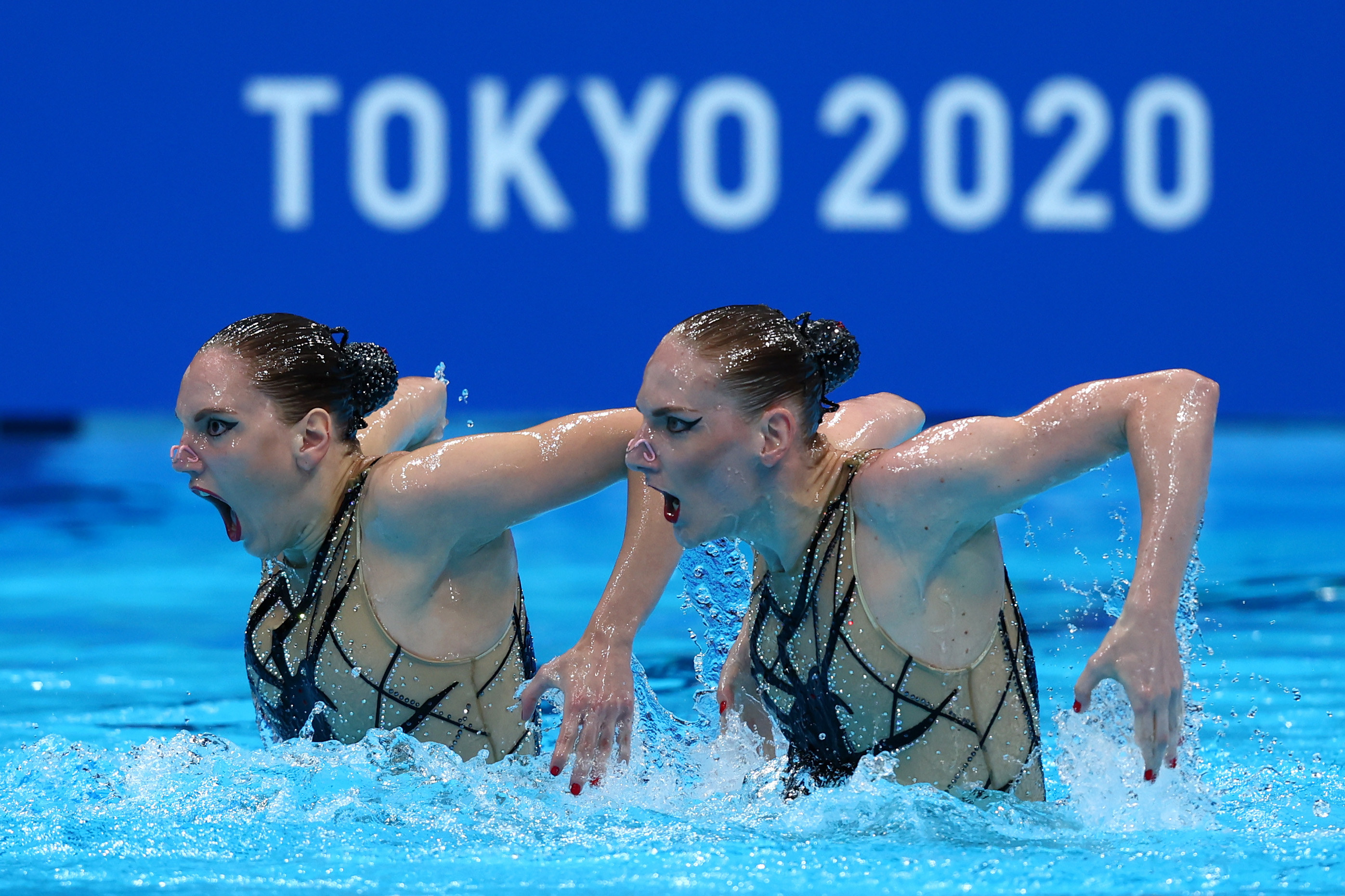 Two swimmers stand side by side with their arms out behind them