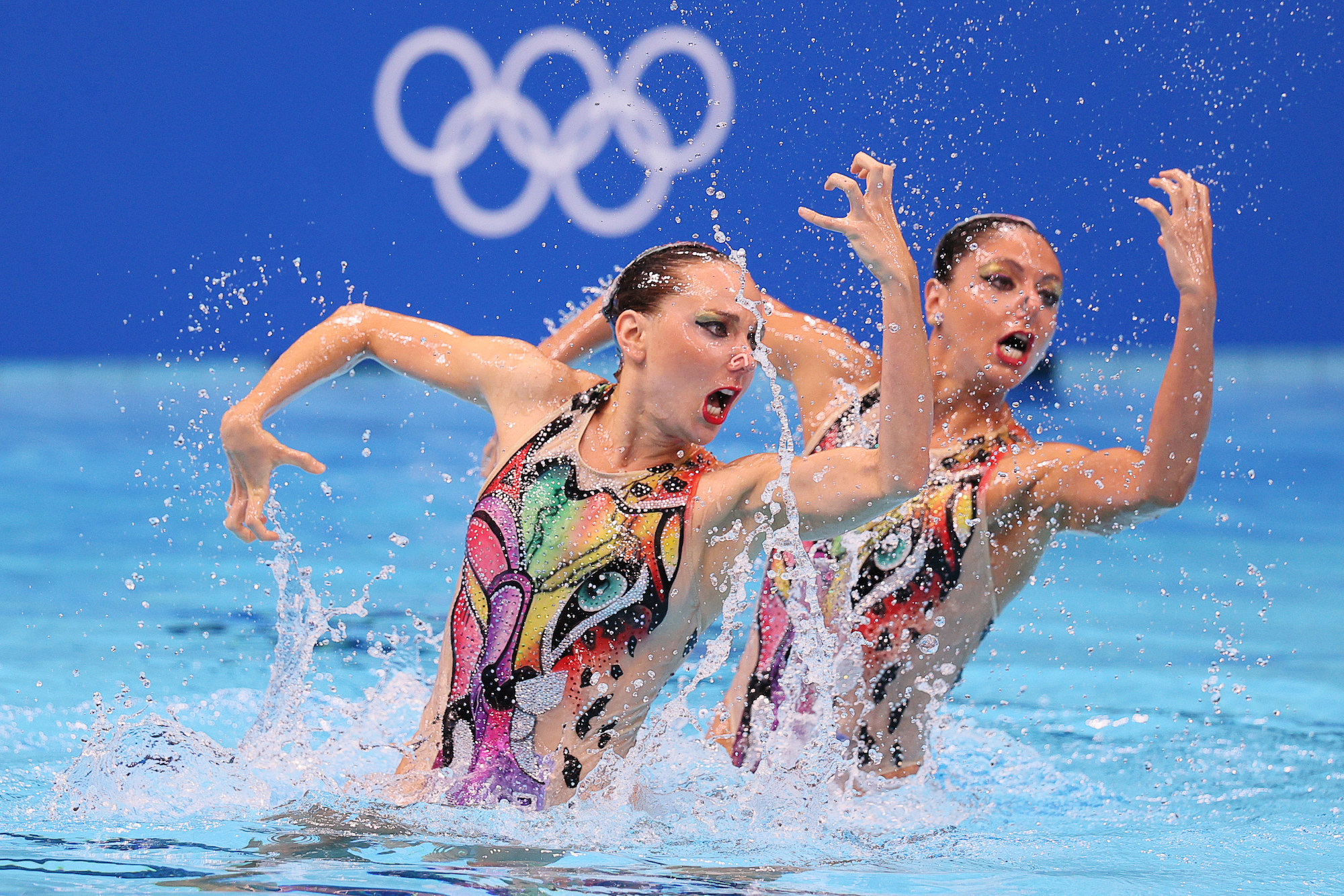 Two women swimmers perform in the pool at the Tokyo Olympics with their arms in front of and behind them