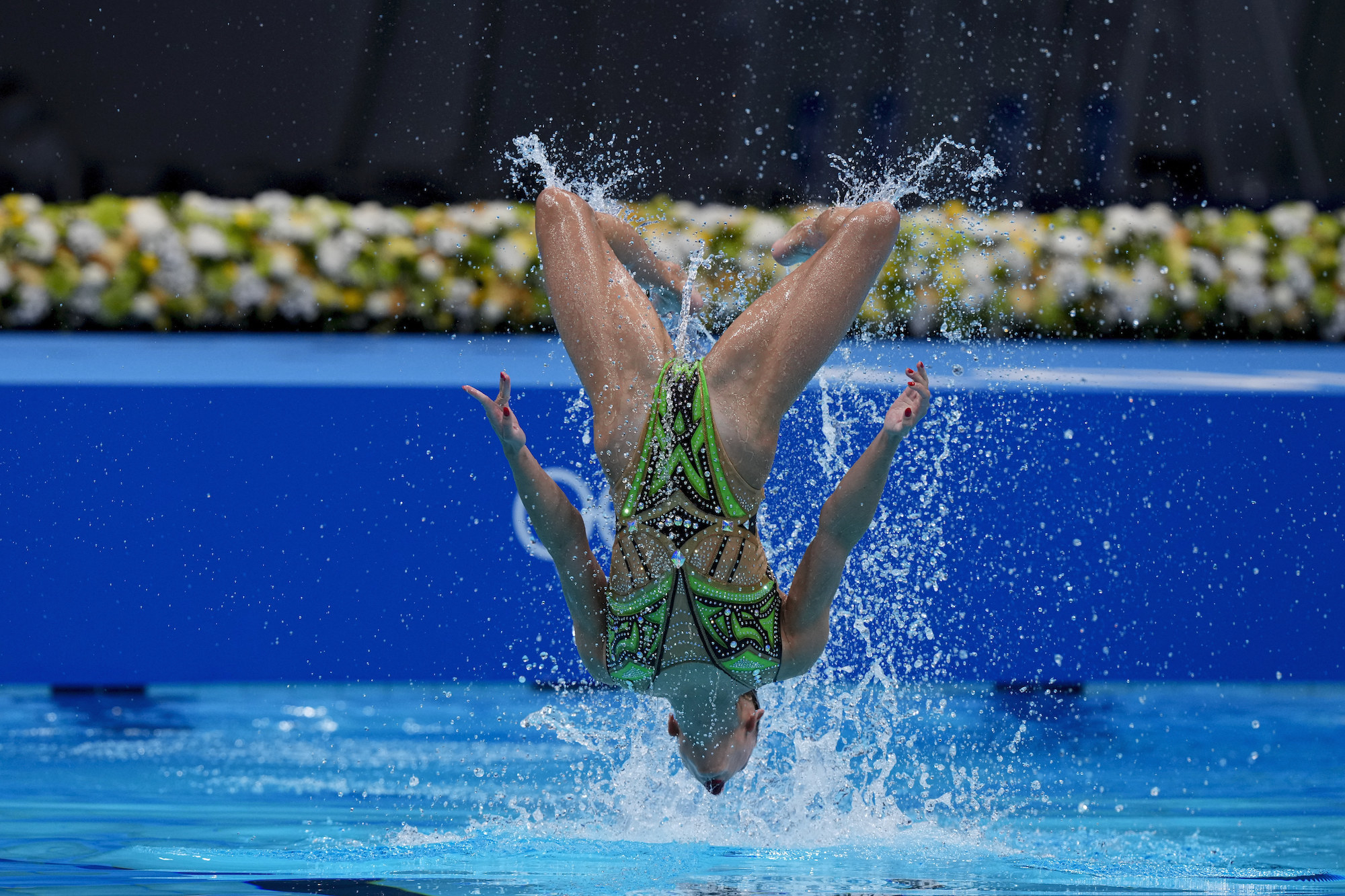 A woman swimmer does a backflip, captured upside-down mid-air