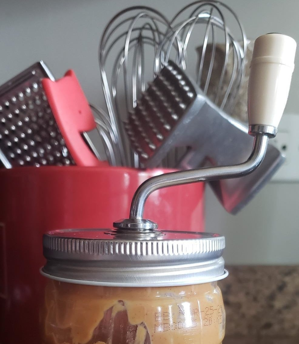 a reviewer photo of the peanut butter mixer on a jar of peanut butter