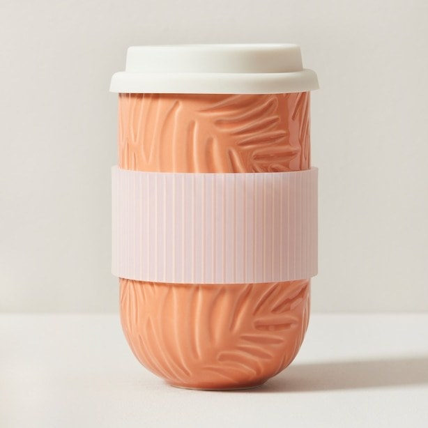 a ceramic tumbler with a silicone lid and holder