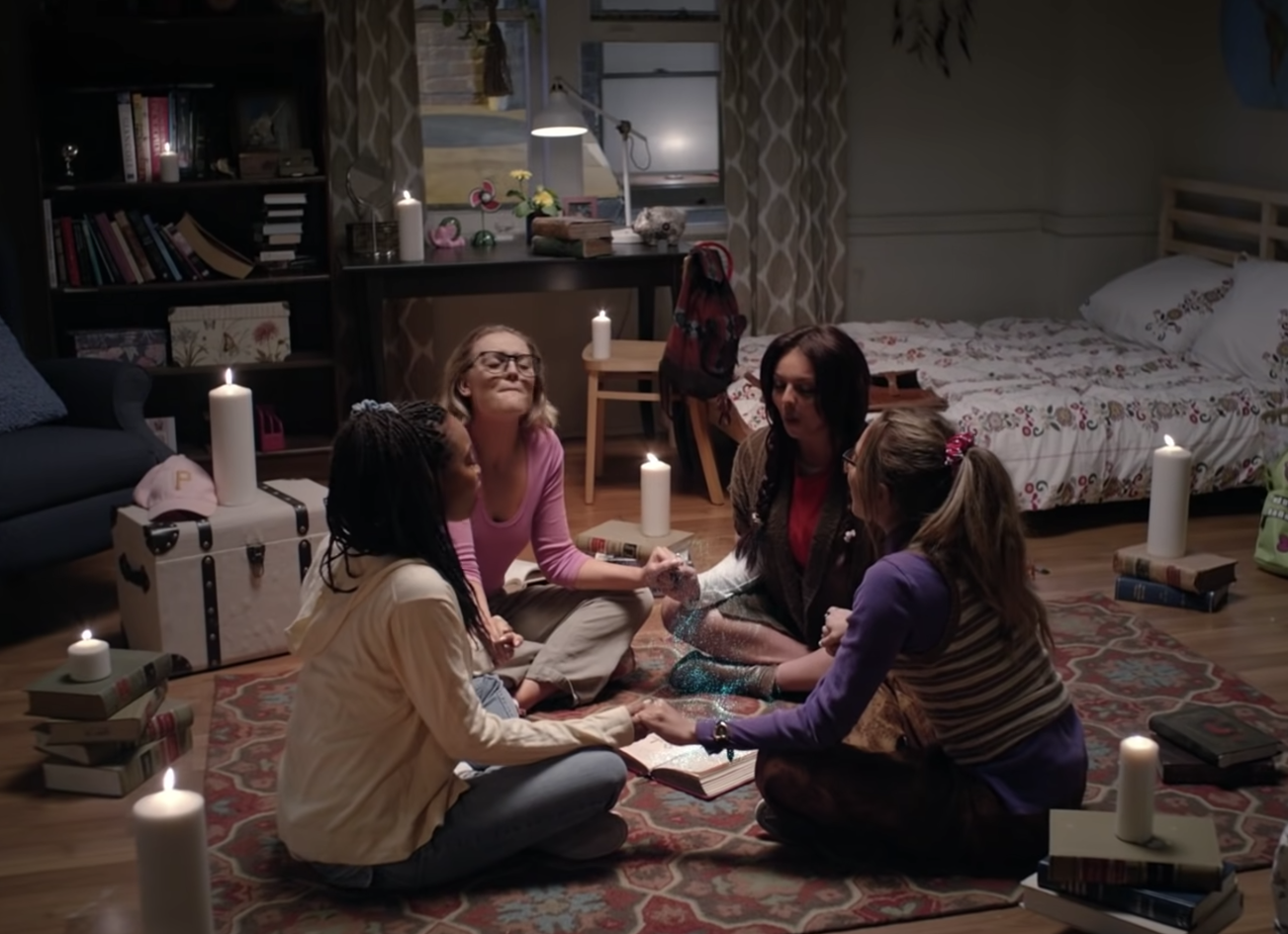 The girls holding hands and doing a spell in the music video