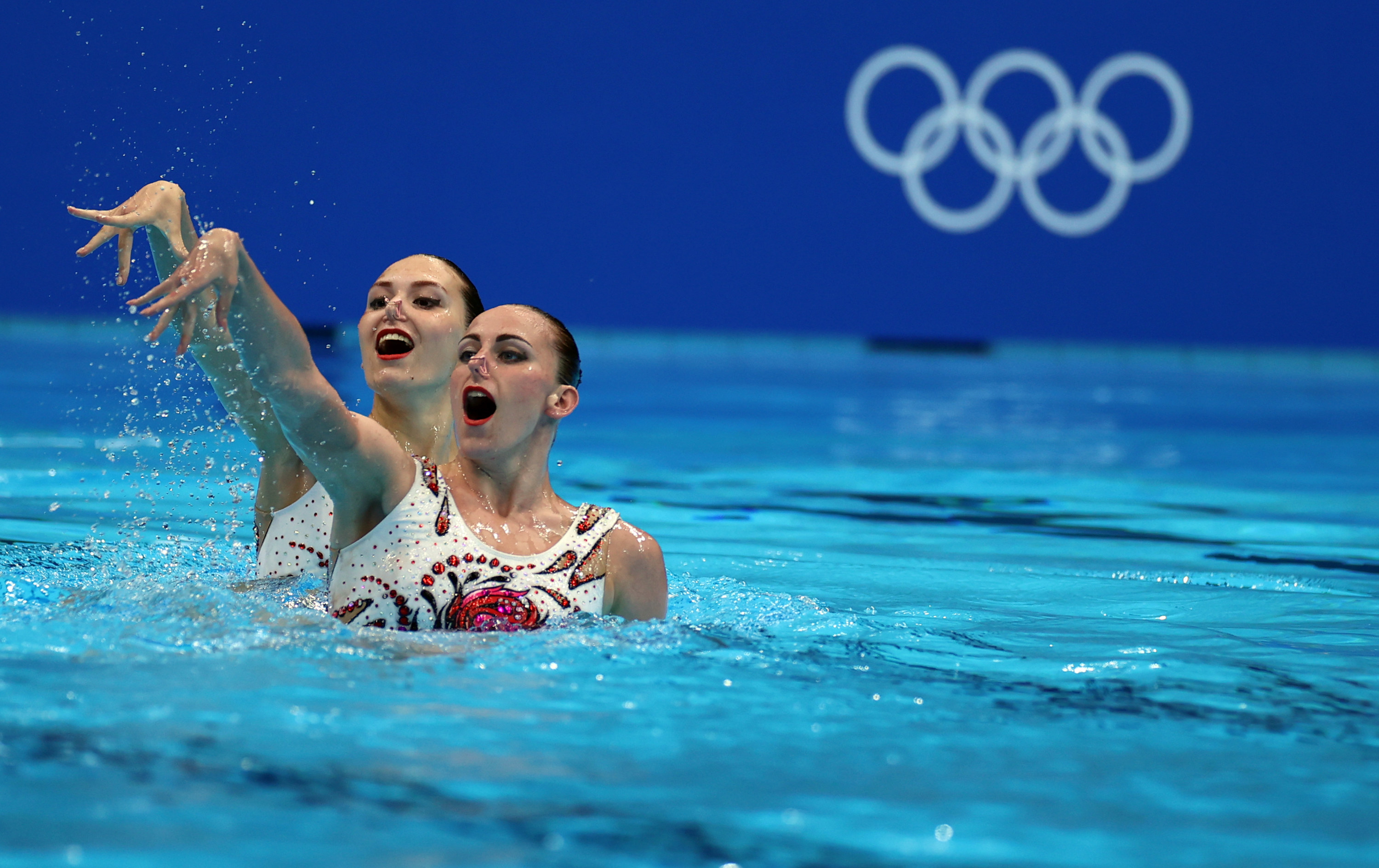 Two swimmers perform in the pool at the Tokyo Olympics