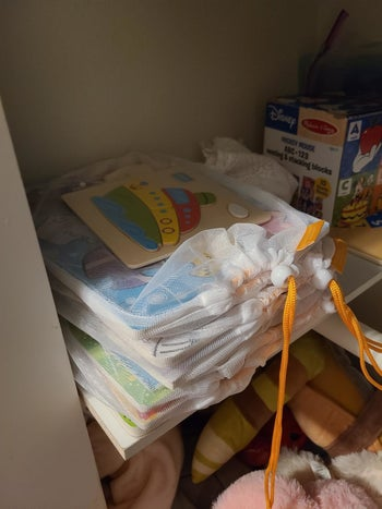 Reviewer's photo showing various puzzles stored in the mesh bags and stacked up on a shelf