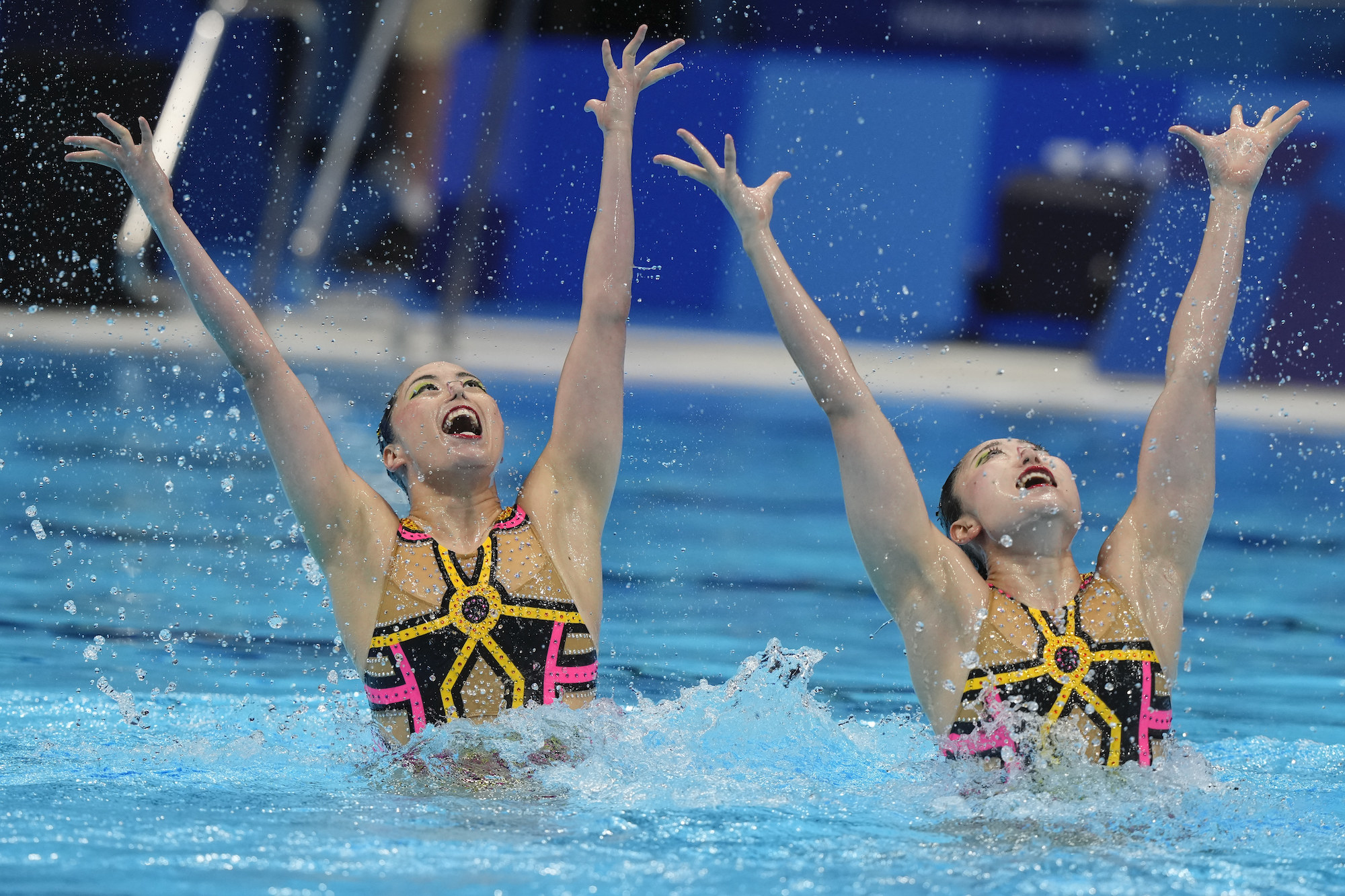 Two swimmers hold their arms above the water in a pool