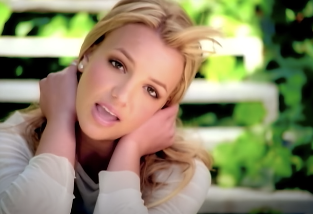 Britney touching her face and singing in the music video