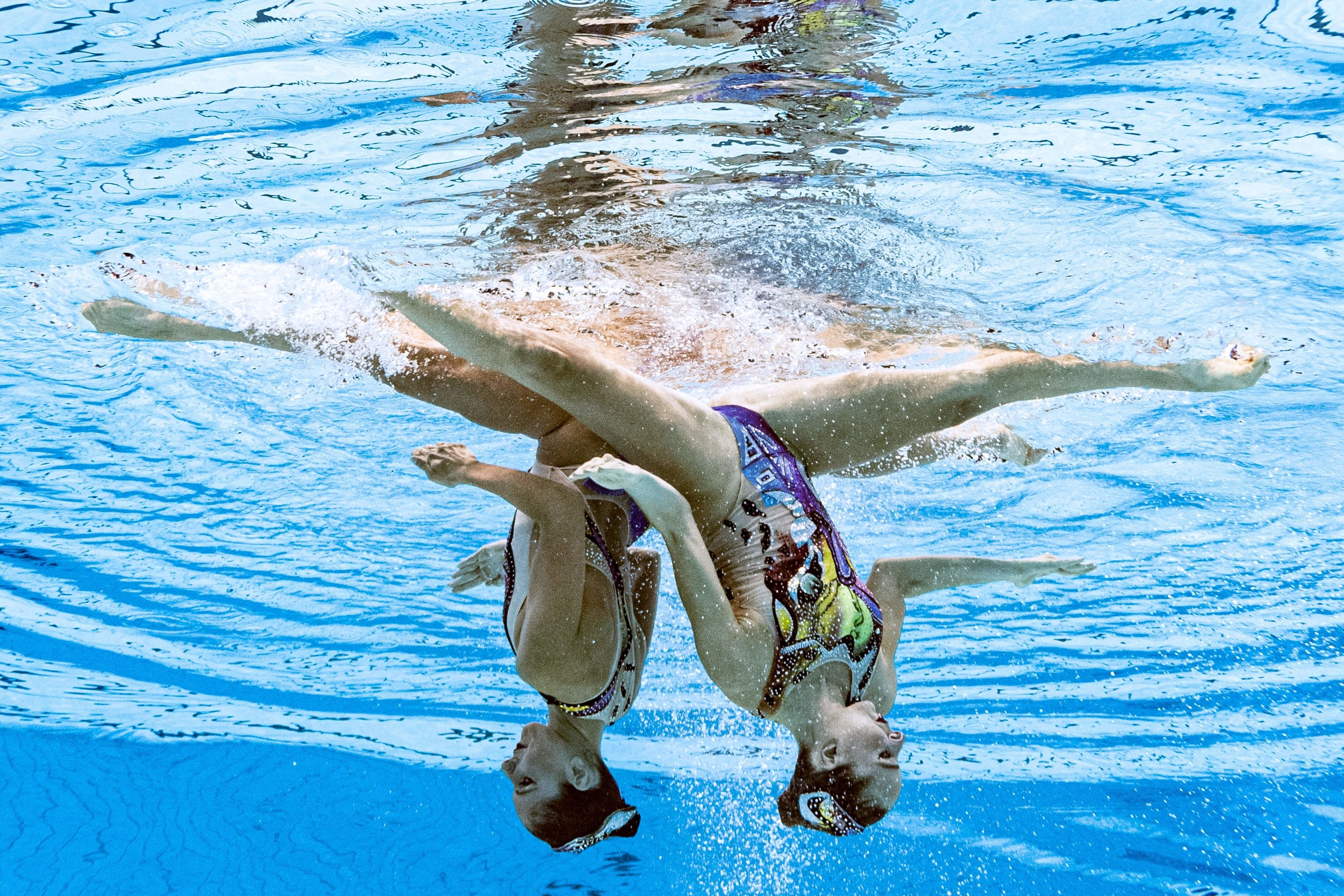 Two women swimmers are upside-down and underwater in a pool