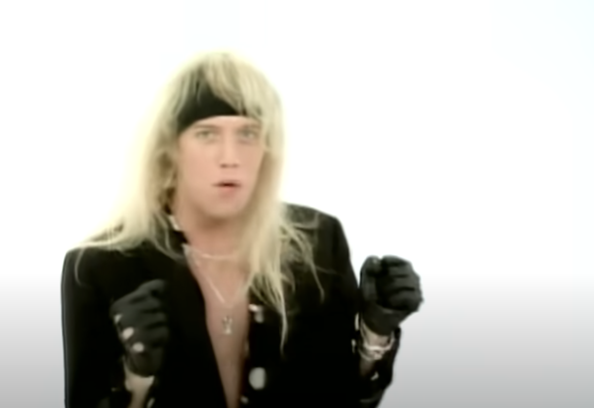 Jani in the music video against a blank backdrop