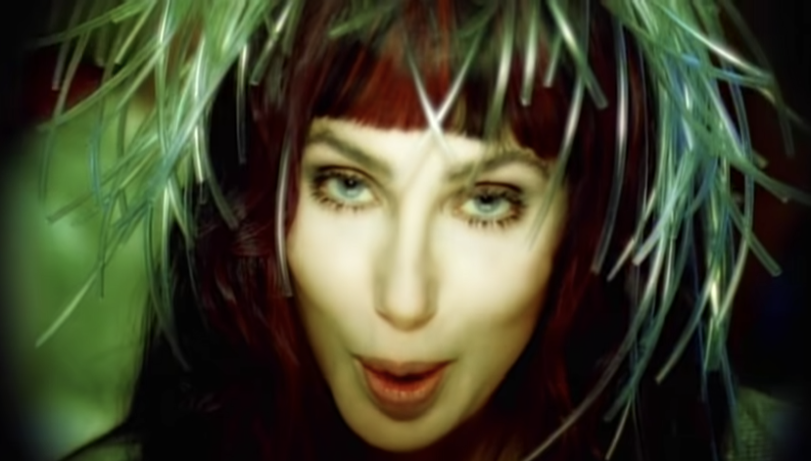 Cher singing in the music video with feathers on her head