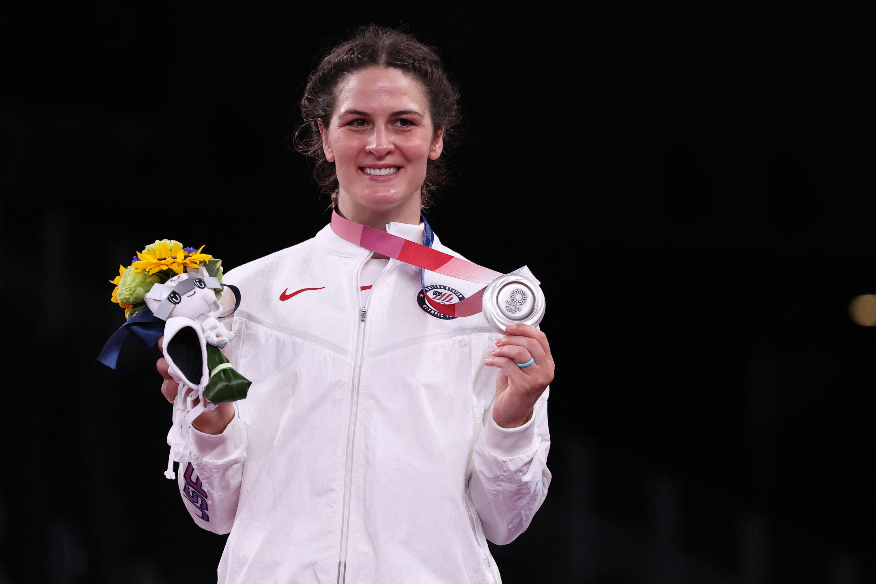 Gray posing on the podium with her silver medal and flowers
