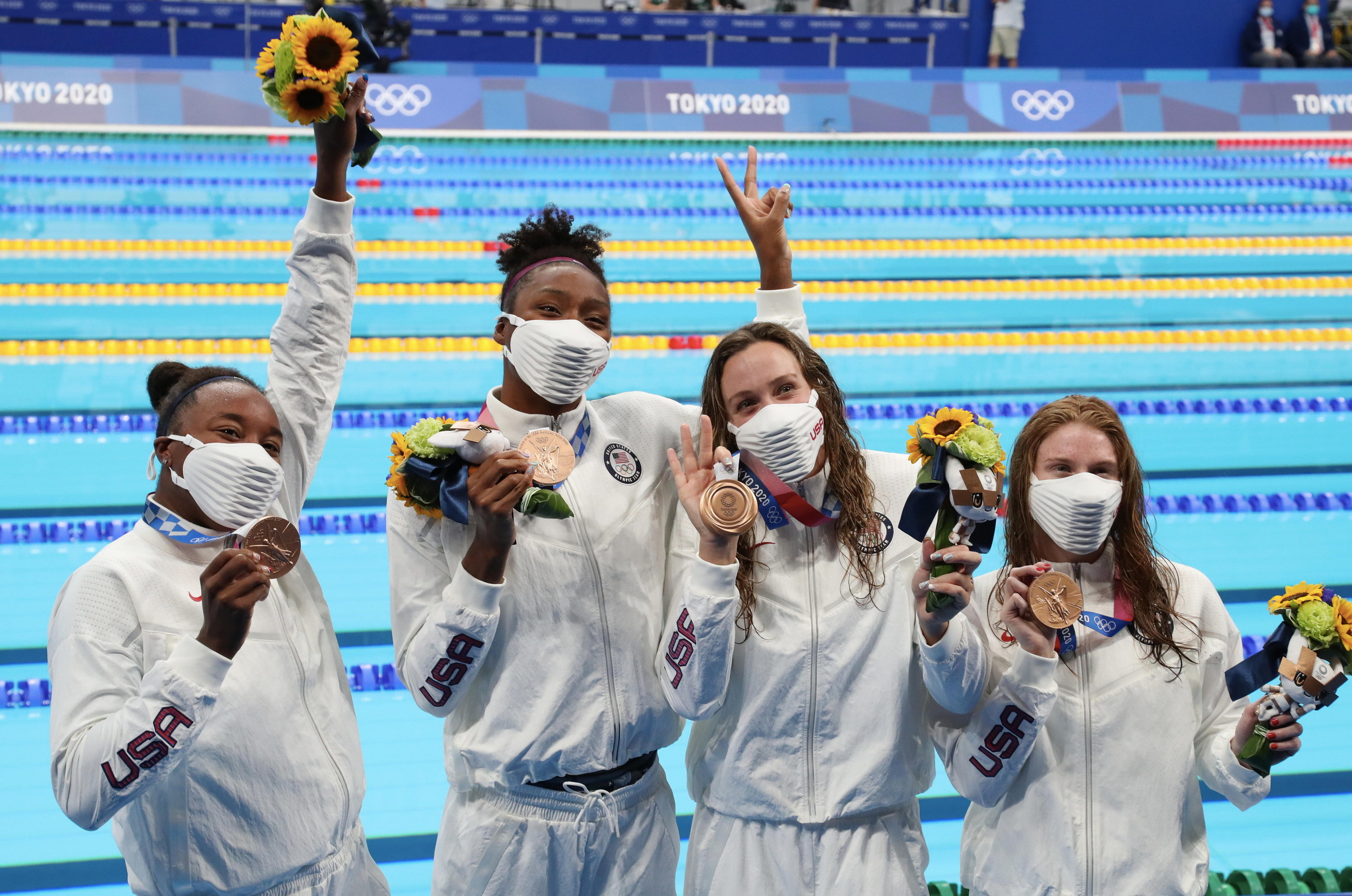 Erika Brown, Natalie Hinds, Abbey Weitzeil and Simone Manuel of Team United States celebrating their bronze medals near the pool