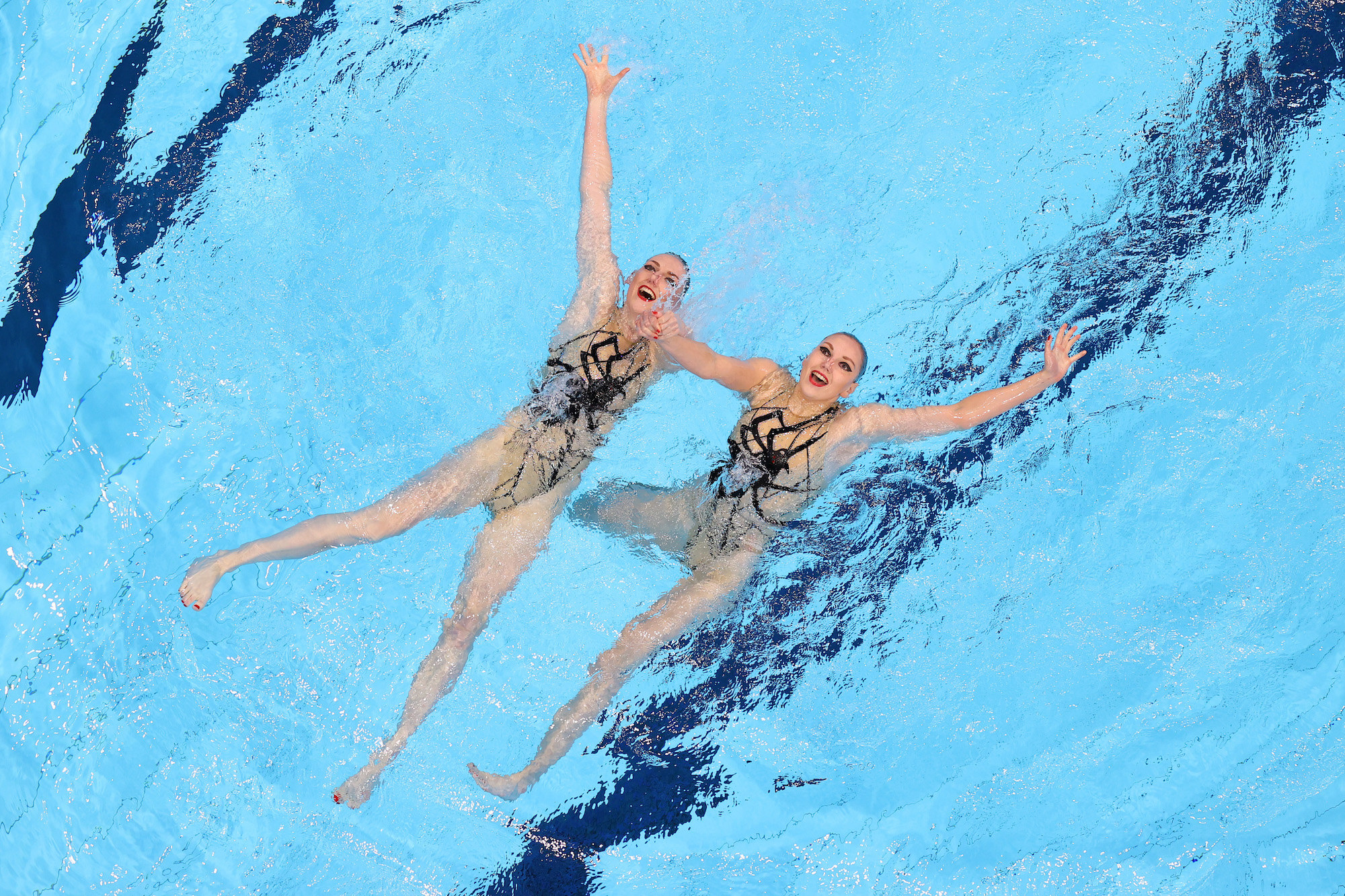 Two women swimmers float on their backs and smile, looking up at the camera