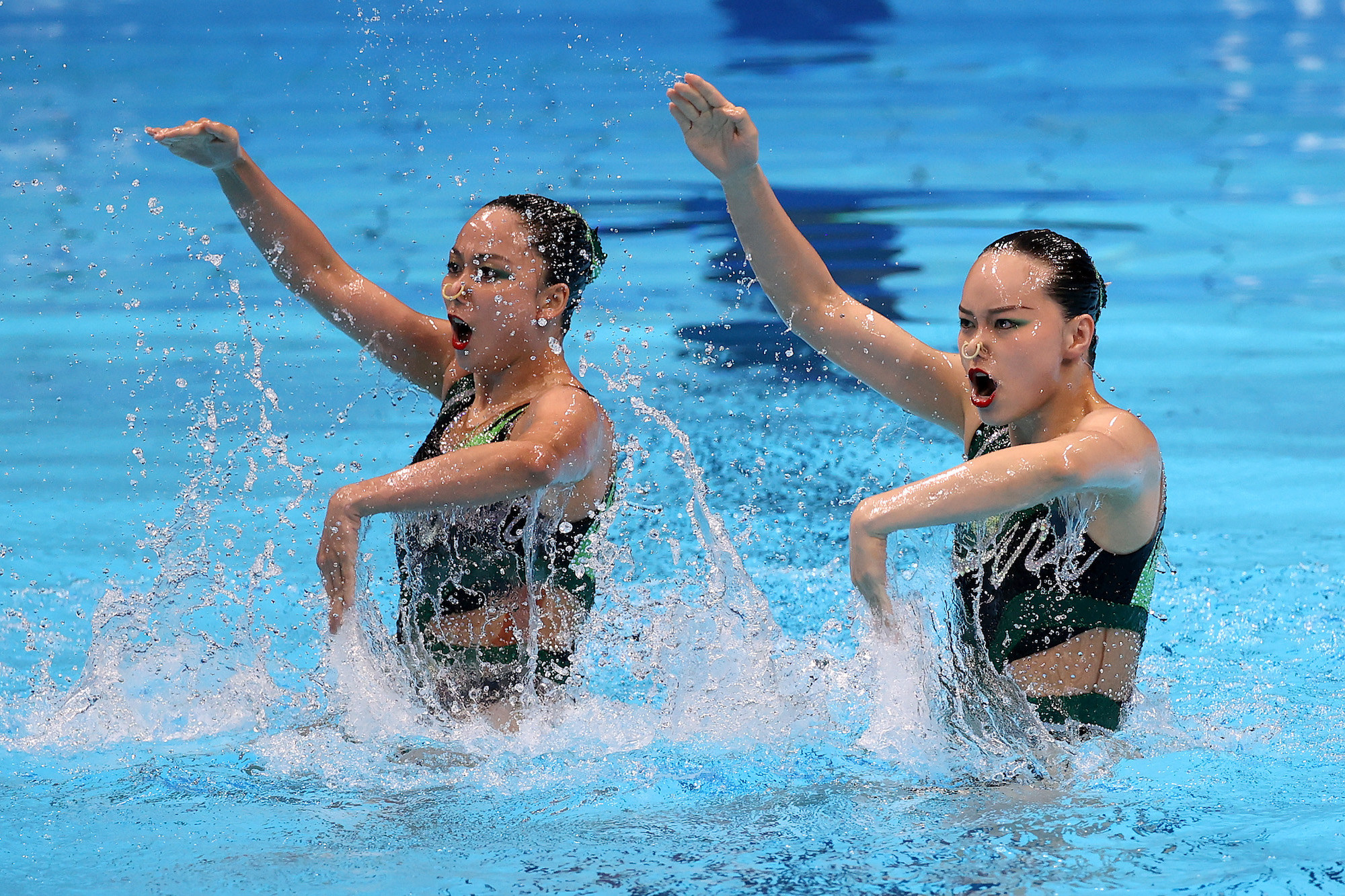 Two women swimmers perform in the pool at the Tokyo Olympics