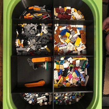 Reviewer's photo showing a storage bin within an Ikea Trofast bin with compartments containing legos